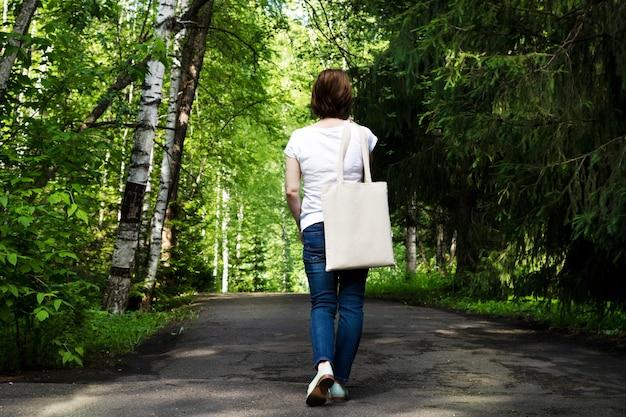 빈 재사용 가능한 쇼핑백 모형을 들고 공원에서 산책하는 여자.