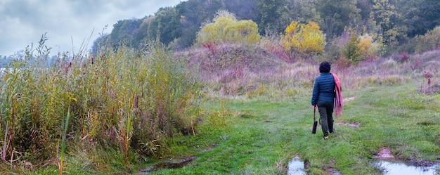 曇りの秋の天気で川と森の近くの野生を歩く女性