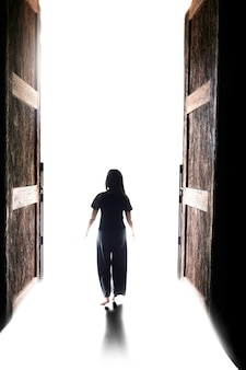 Woman walking into the light through the open big door