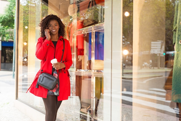 Woman walking near showcase and talking by smartphone