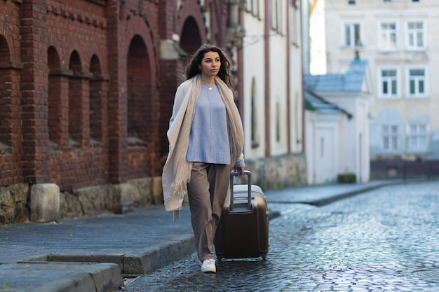Woman walking in a new city with a phone in her hands and a suitcase