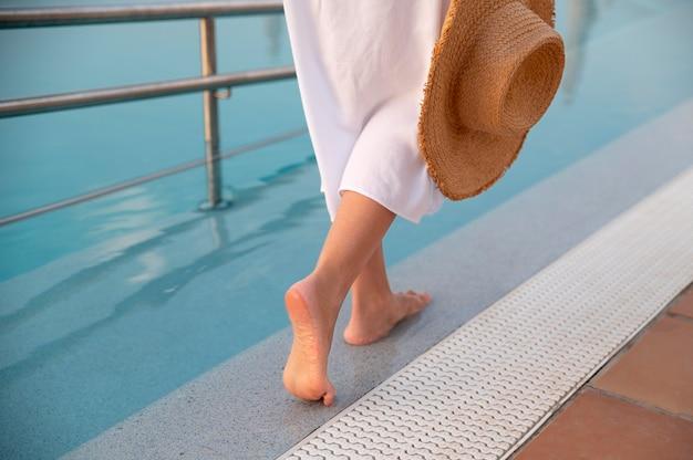 麦わら帽子をかぶってプールの横を歩く女性