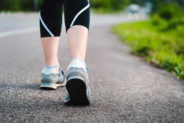 田舎道を歩く女性女性の足の背面図運動を伴うヘルスケアの概念