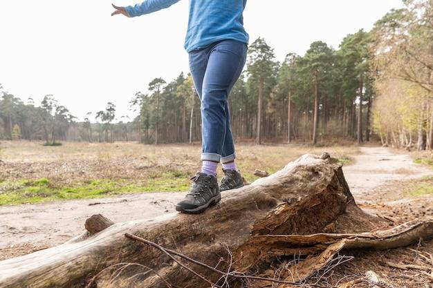 倒れた木を歩く女性