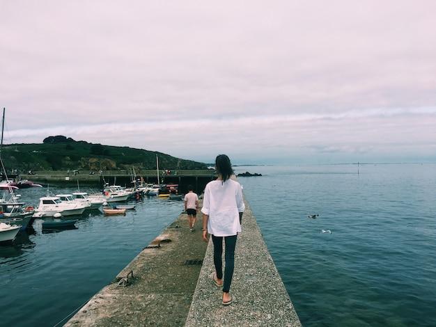 海の真ん中にある小道を歩く女性