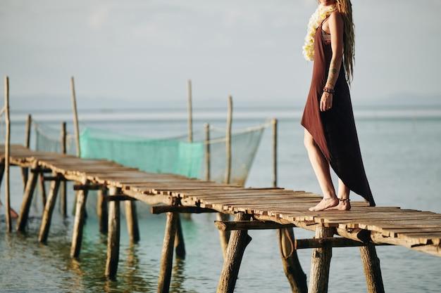 狭い木製の桟橋を歩いて女性