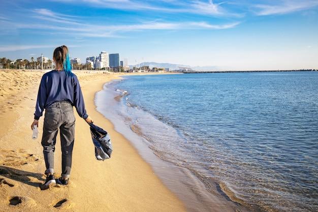 ビーチを歩いて、黒いゴミ袋でビーチを掃除しているゴミやペットボトルを拾う女性