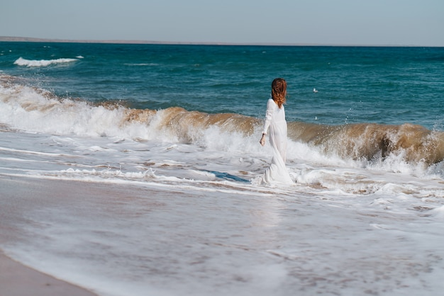 Женщина гуляет на пляже летом