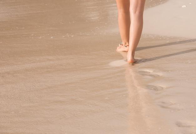 발자국을 떠나 해변을 걷고 여자
