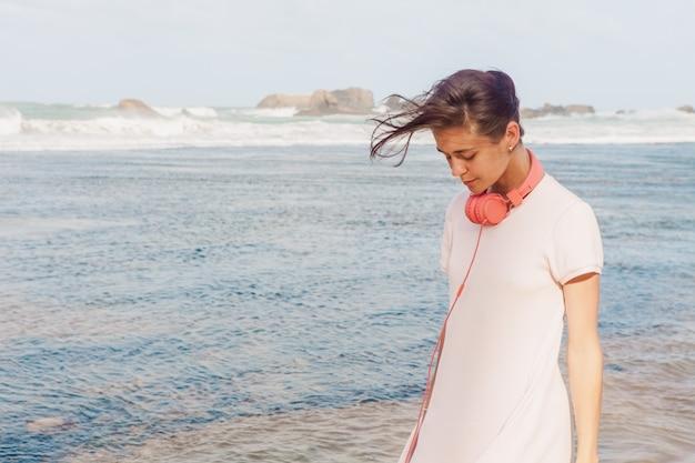 Женщина гуляя на песок пляжа