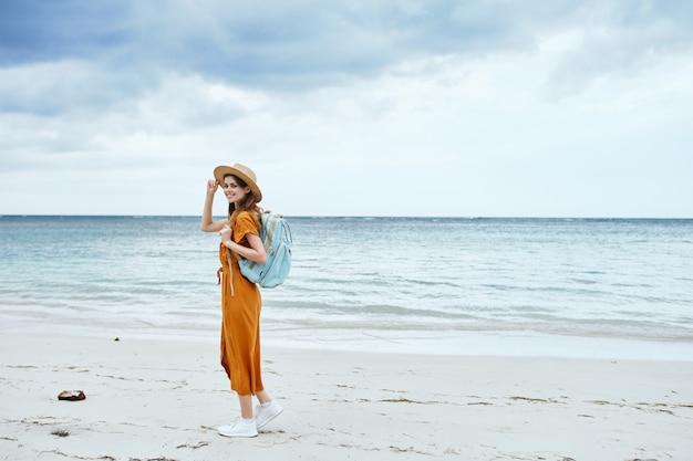 Женщина гуляет по пляжу туризм отпуск рюкзак путешествия пейзаж океан