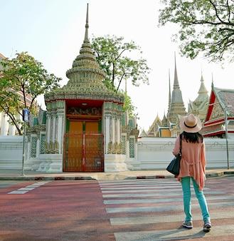 タイ、バンコクのワットポーの豪華な門や涅槃仏の寺院に続く横断歩道を歩いている女性