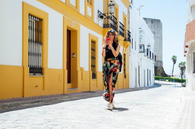 彼女のスマートフォンを見ている通りを歩いている女性