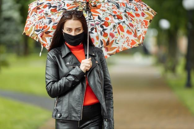Женщина идет по улице в защитной маске
