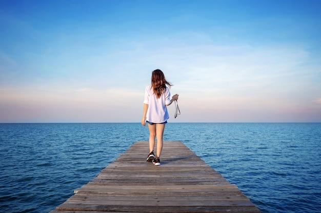 木の橋を歩いている女性が海に伸びていた。