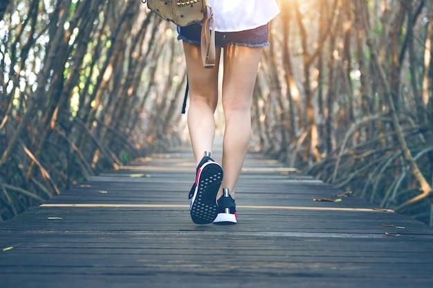 목조 다리에 걷는 여자. 빈티지 톤.