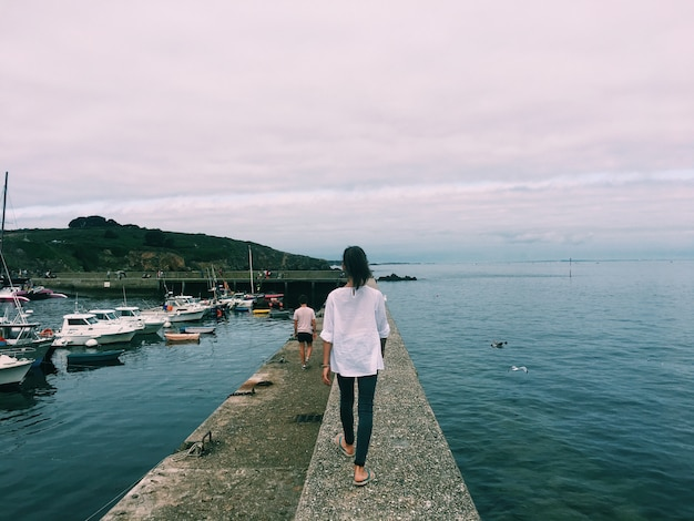 Woman walking on a pathway in the middle of the sea