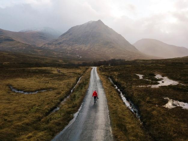Donna che cammina su una strada a glen etive, scozia