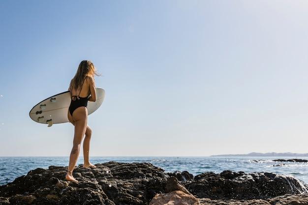 Woman walking on rocky sea shore with surfboard