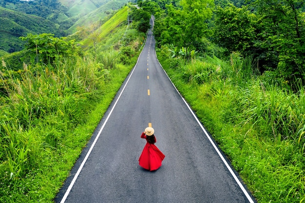 Woman walking on sky road over top of mountains with green jungle in nan province, thailand