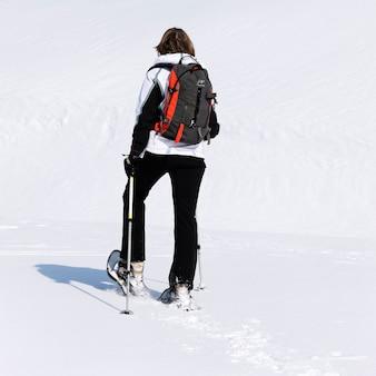 Donna che cammina nella neve con le racchette