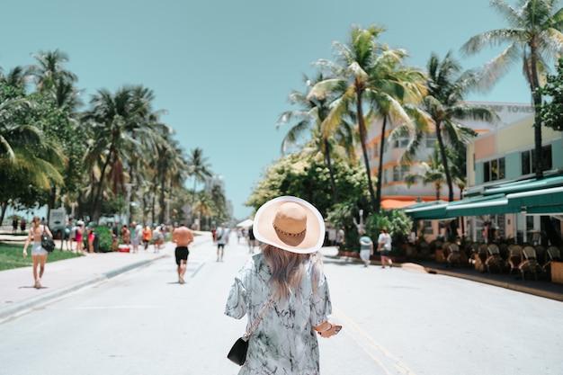 マイアミビーチのヤシの木の休暇を歩く女性