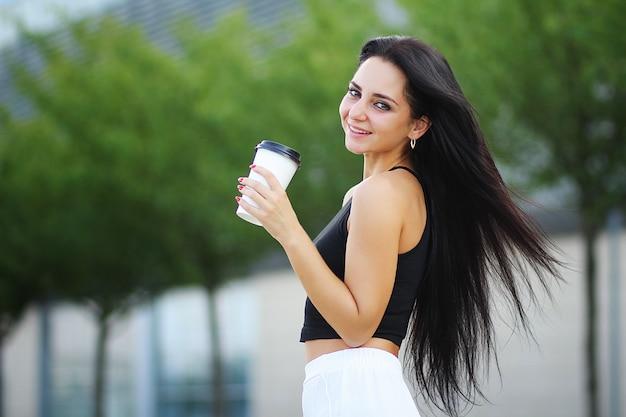 Woman walking on the street with take away coffee