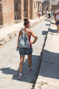 イタリアのポンペイのローマ遺跡を歩いている女性。
