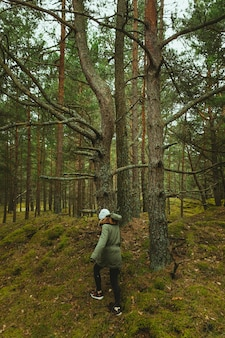 森の木々を歩く女性