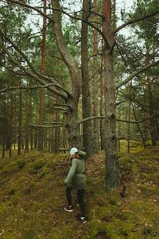 Donna che cammina tra gli alberi della foresta