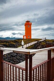 アイスランドの木製の橋でオレンジ色の灯台に歩いている女性