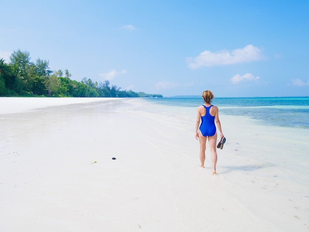 Woman walking on tropical beach. rear view white sand beach turquoise trasparent water caribbean sea real people. indonesia kei islands moluccas travel destination.