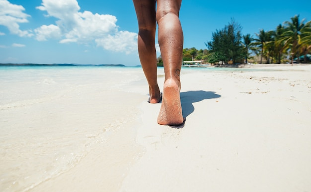 Woman walking on a tropical white sand beach