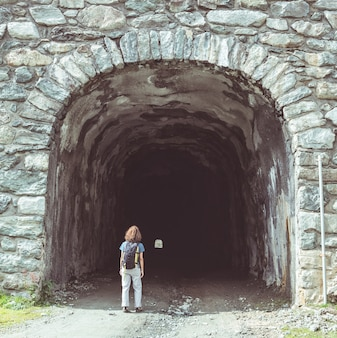 Woman walking at tunnel entrance. toned image, vintage filter, split toning.