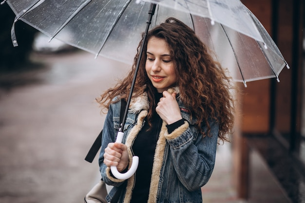 Woman walking under the umbrella in a rainy weather