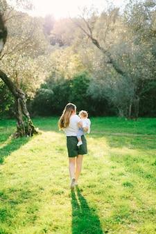 그녀의 팔에 그녀의 딸과 함께 올리브 나무 아래 산책하는 여자