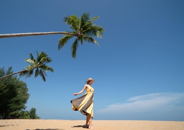 Женщина, идущая под кокосовой пальмой на песчаном пляже с голубым небом.