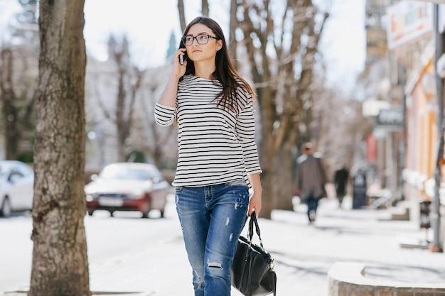 Donna che cammina mentre parla sul suo telefono