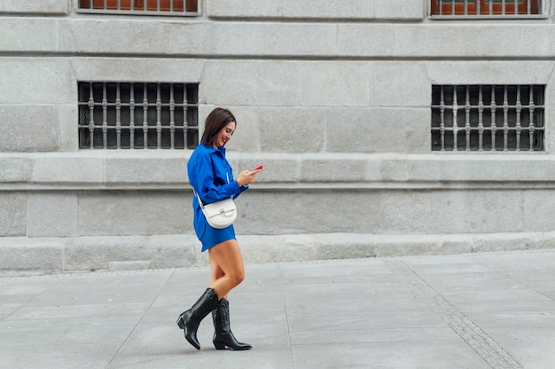 携帯電話で入力しながら歩く女性