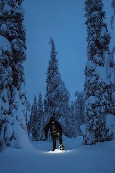 フィンランドの雪に覆われたリーシトゥントゥリ国立公園でヘッドランプを持って歩く女性