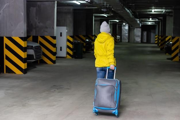 지하 주차장에 가방을 걸어 여자