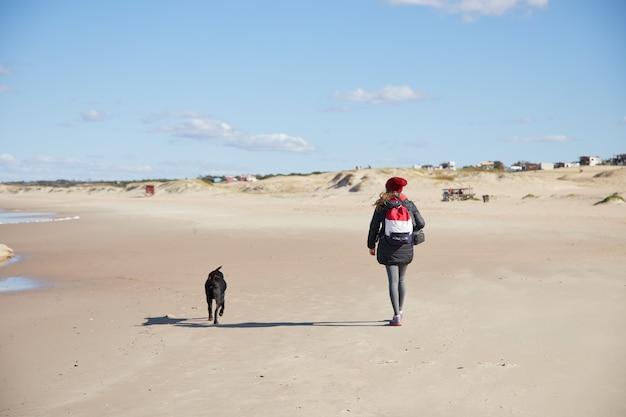 흐린 하늘 아래 겨울에 해변에서 강아지와 함께 산책 하는 여자.