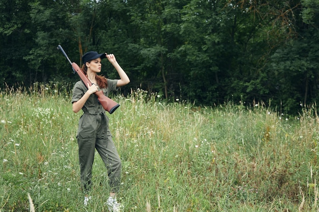Woman walking with a gun in nature hunting lifestyle green overalls