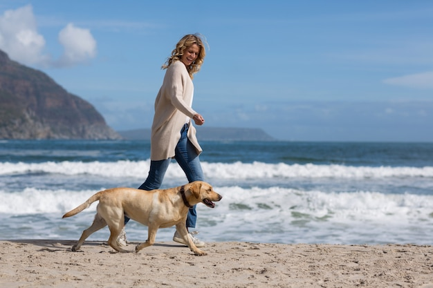 Woman walking with her dog on the beach