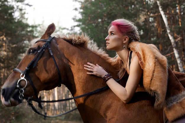 Woman walking with horse autumn on nature. creative hot pink makeup woman face, hair coloring. portrait of a woman with a horse. horse riding in the autumn forest