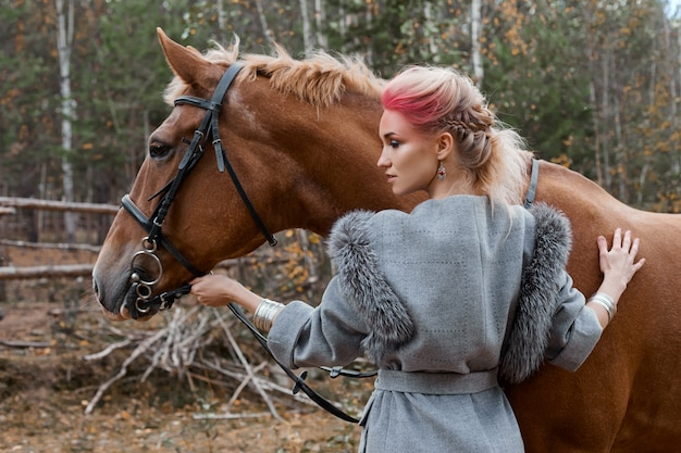 Woman walking with horse autumn on nature.