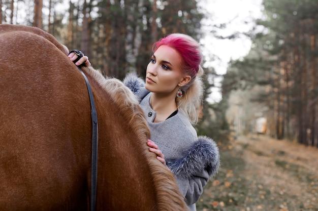 Женщина гуляет с лошадью осенью на природе. творческий ярко-розовый макияж лицо девушки, окраска волос. портрет девушки с лошадью. верховая езда в осеннем лесу. осенняя одежда и ярко-красный макияж