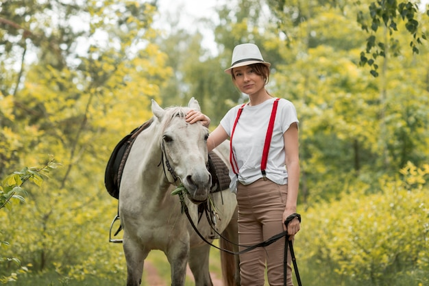Woman walking with a horse in the countryside