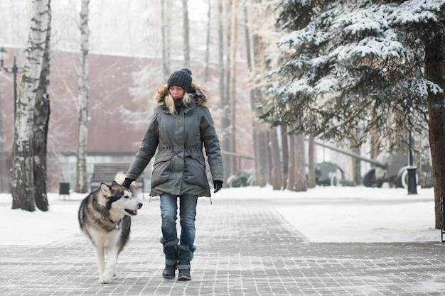 겨울에 허스키 강아지와 함께 산책하는 여자.