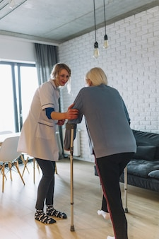 Woman walking with nurse in retirement home